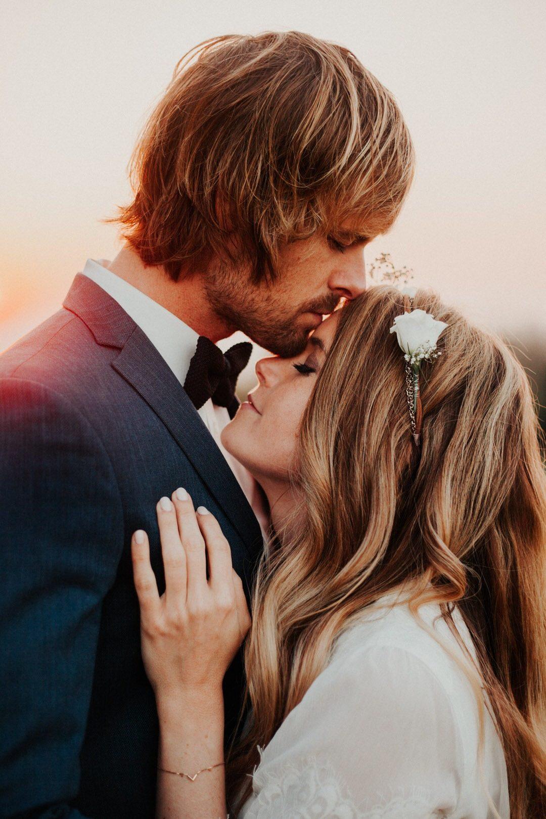 Zärtlicher Kuss von Bräutigam auf die Stirn seiner Boho-Braut.