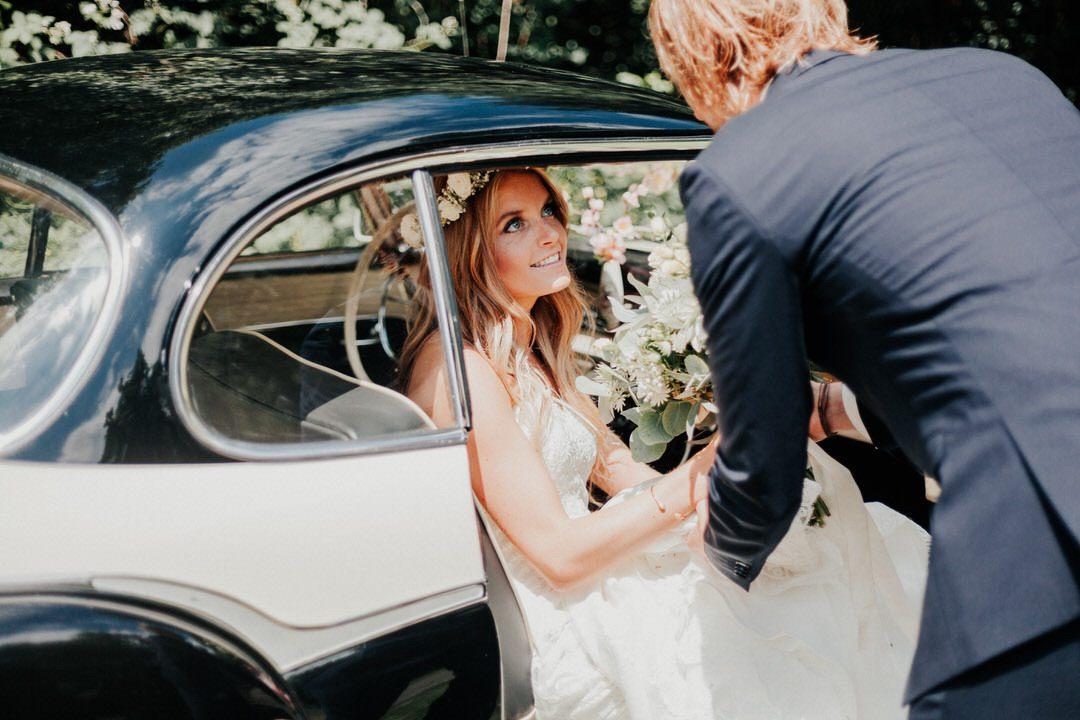 Romantischer Moment, als der Bräutigam seiner Braut bei einer Boho-Hochzeit aus dem Borgward Oldtimer hilft