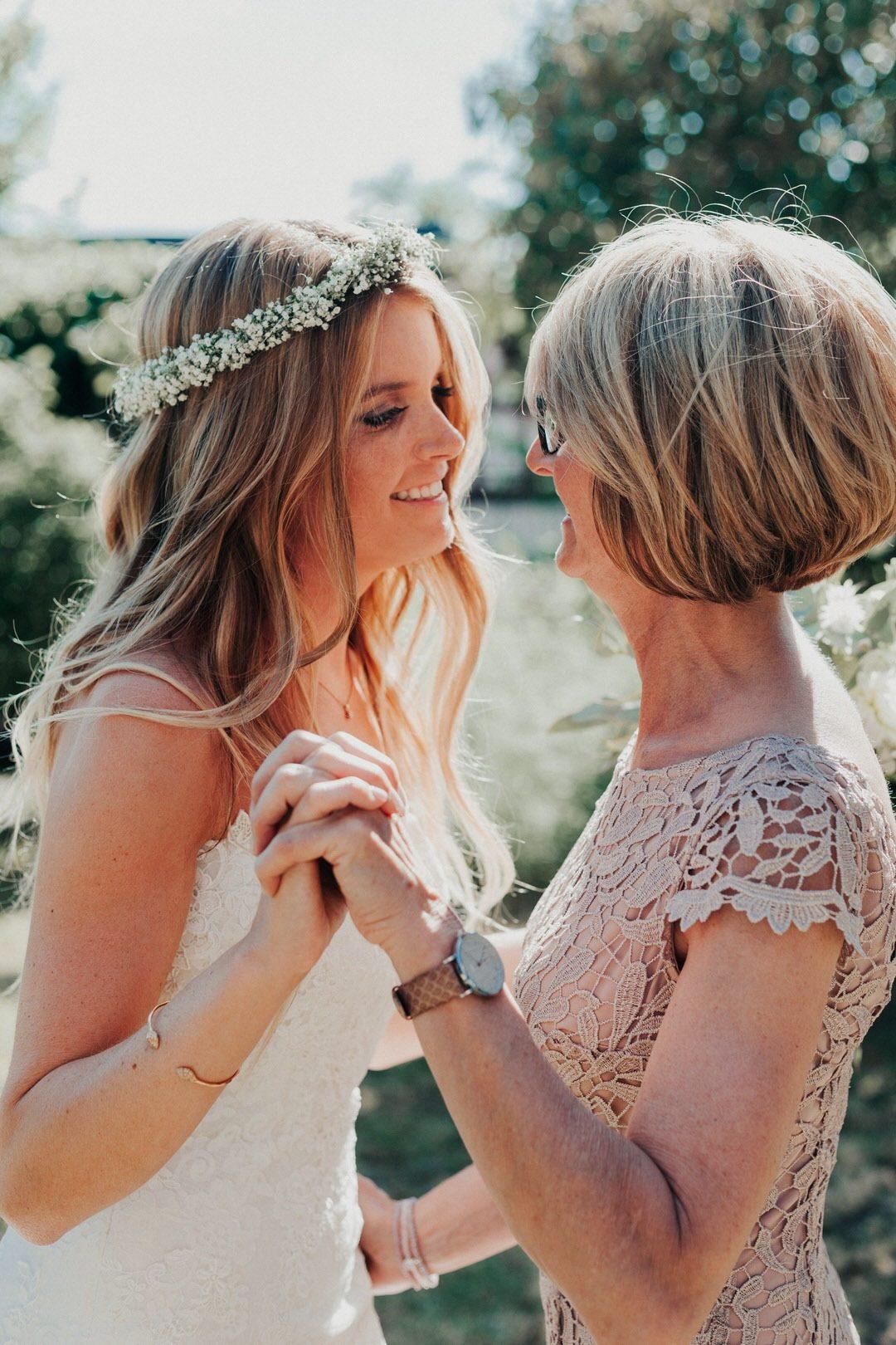 Candid Boho-Wedding Moment, Boho-Braut Hand in Hand mit ihrer Mutter