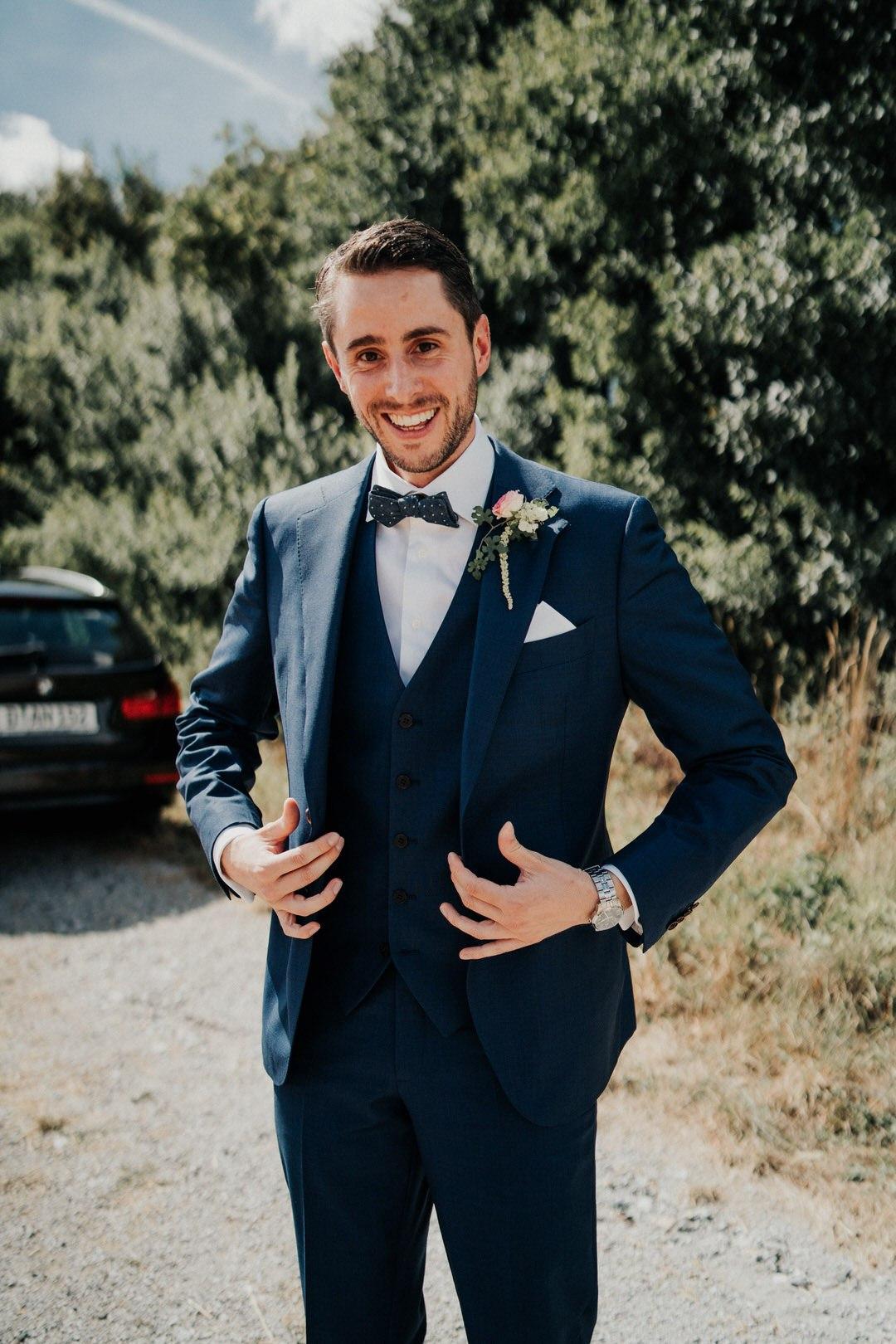 Bräutigam in stilvollem blauen Anzug mit altrosaner Rose als Anstecker