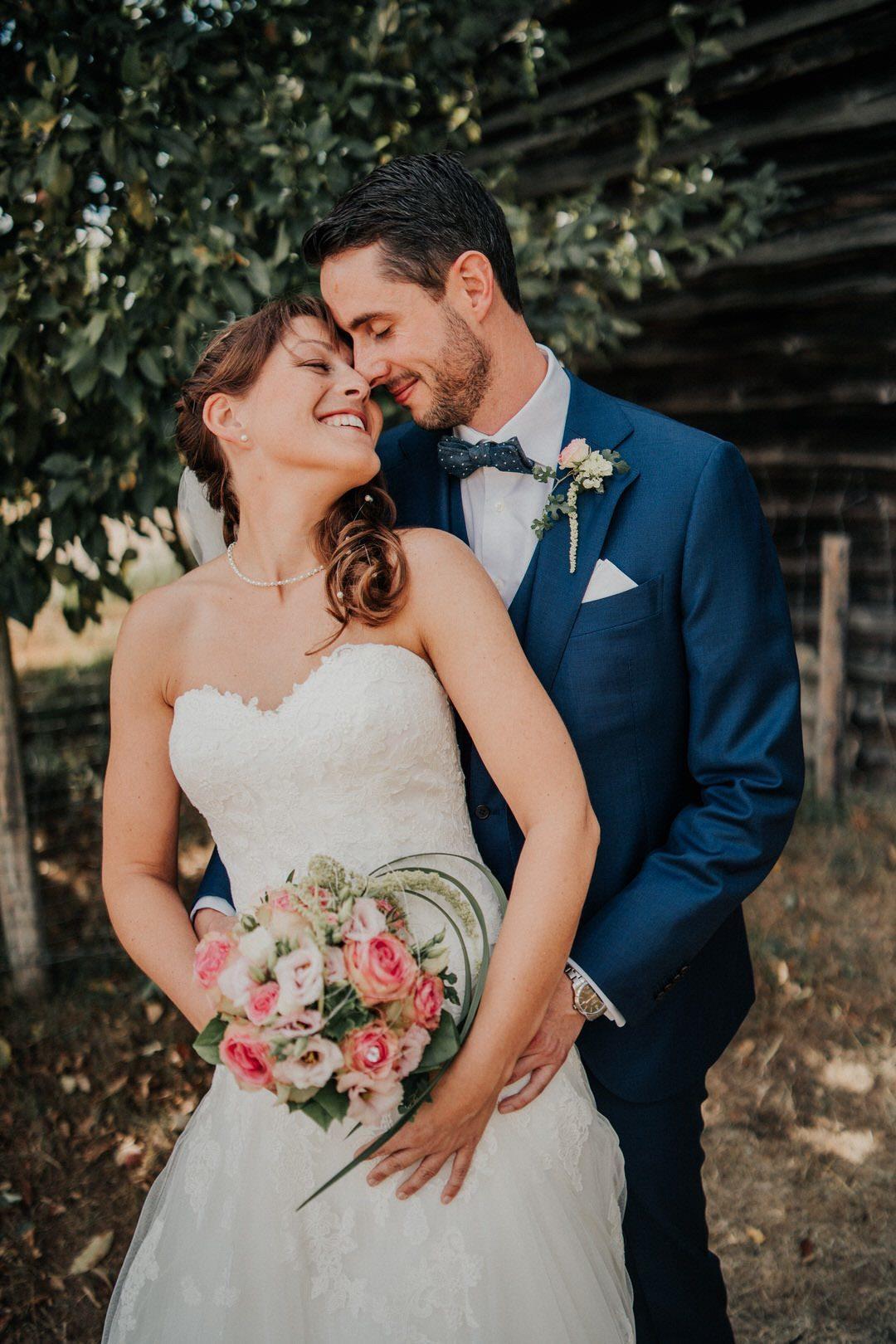 Strahlende braut und glücklicher Bräutigam Stirn an Stirn beim Hochzeits-Paarshoot