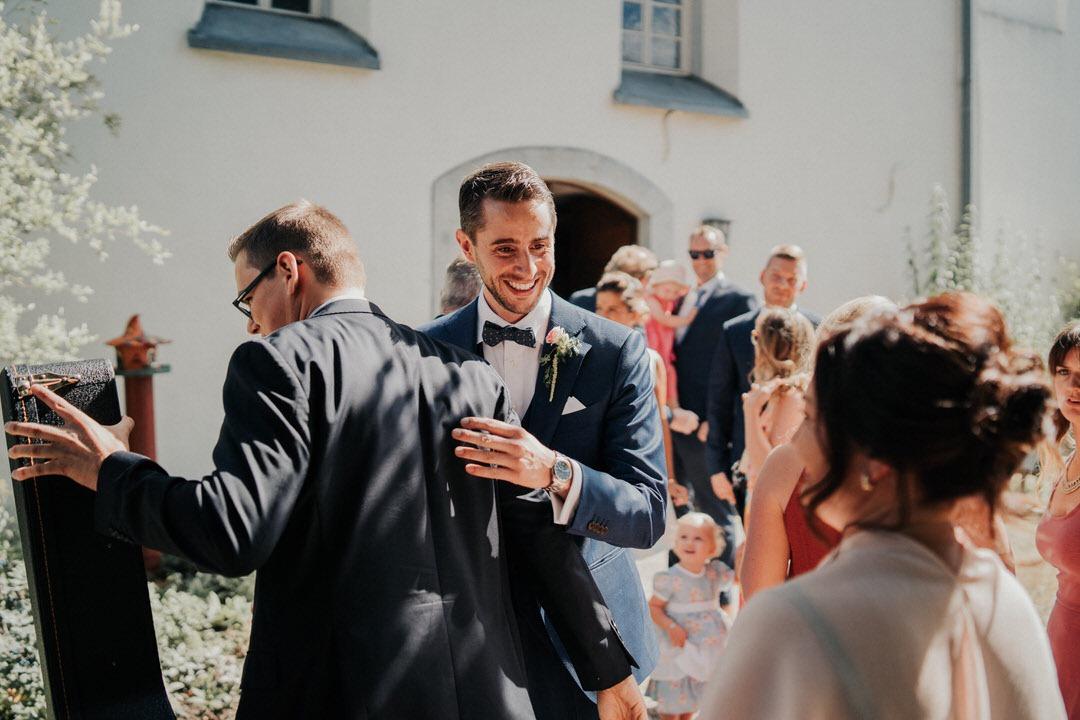Bräutigam empfängt die Gäste vor der St Nikolaus Kirche in Hahnstätten bei Wiesbaden