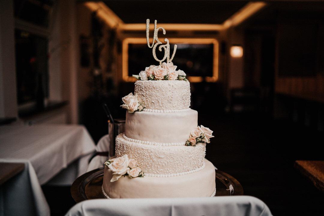 Detail Hochzeitsfotos von der Vintage-Hochzeitstorte mit altrosa-farbenen Rosen, weißen Verzierungen und goldenen Anfangsbuchstaben des Brautpaars bei einer italienischen Hochzeitsfeier in Gießen