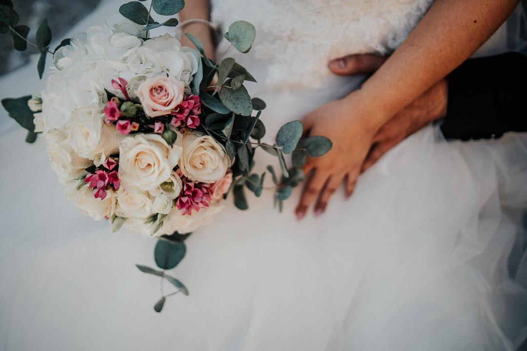 Vintage Hochzeitsdetails der Brautpaar-Hände mit Strauß
