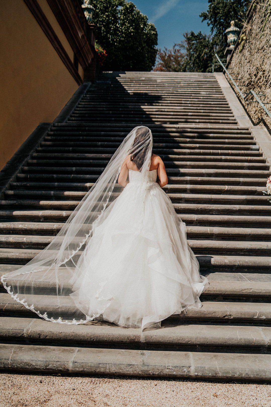 Italienische Vintage-Braut auf dem Weg die Treppe hoch mit Wind im Schleier