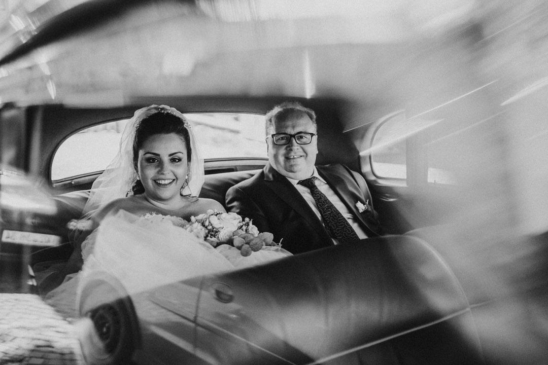 Hochzeitsbild von der italienischen Braut mit dem Brautvater im Oldtimer vor der Hochzeitszeremonie