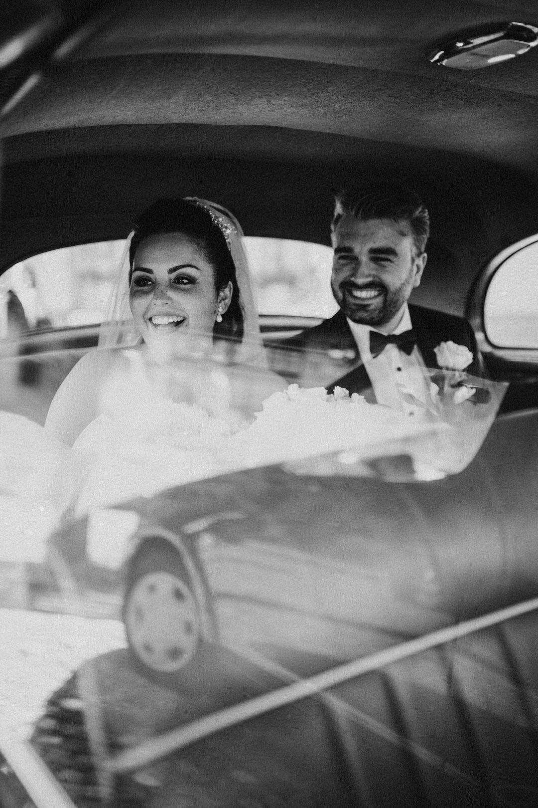 Hochzeits-Reportagefoto von Braut und Bräutigam nach der Trauung im Oldtimer, den Gästen winkend