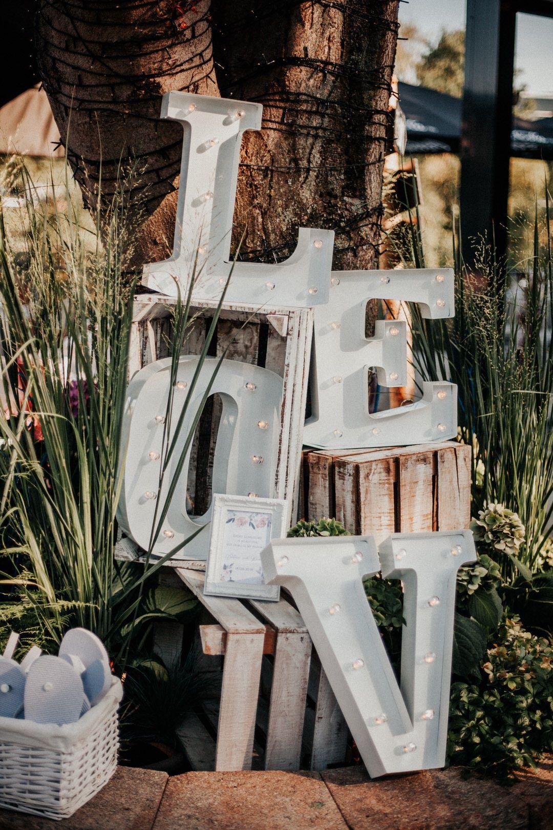 LOVE beleuchtete Neon Buchstaben als Dekoelement für eine Vintage-Boho-Hochzeit