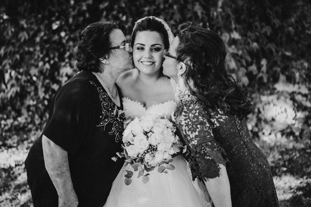 Oma und Mama küssen die italienische Braut auf die Wange, ein traditionelles Hochzeitsbild
