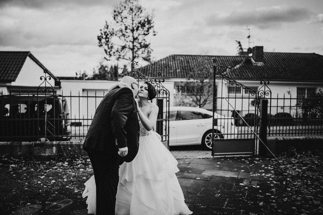 Winterhochzeit: Brautvater begrüßt Braut vor Kirche