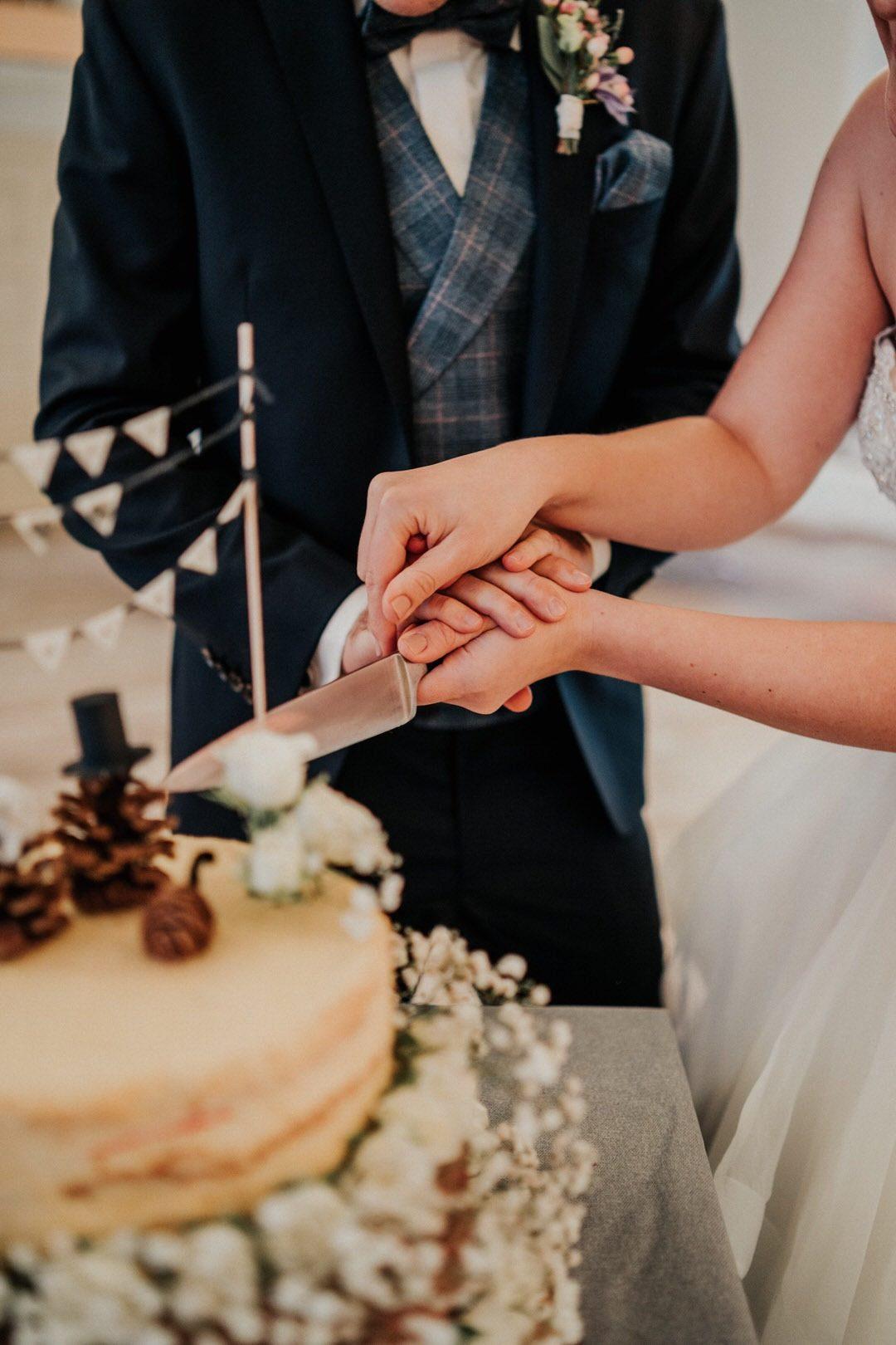 Anschneiden der winterlichen Hochzeitstorte durch das Brautpaar