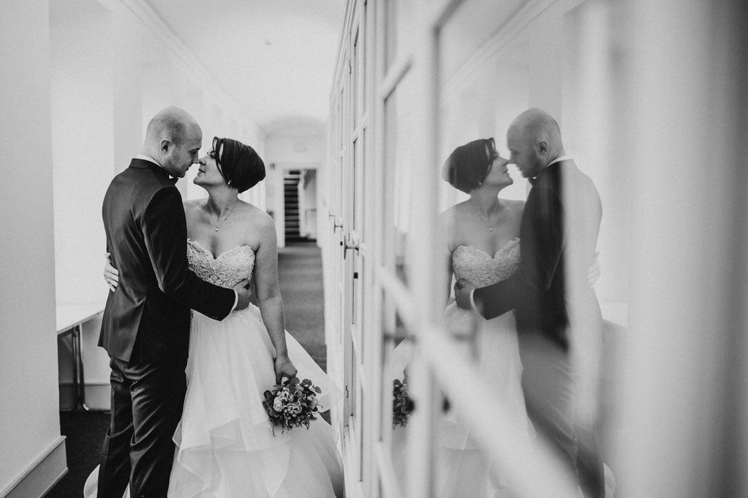 Bilder mit Spiegelung des BRautpaars im Fensterglas beim Hochzeitsshooting im Winter