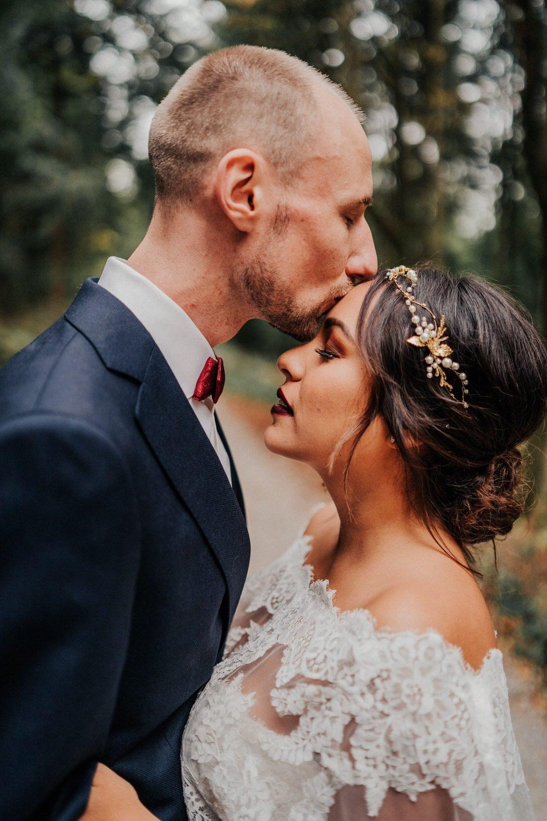 Bräutigam küsst Boho-Braut auf die Stirn