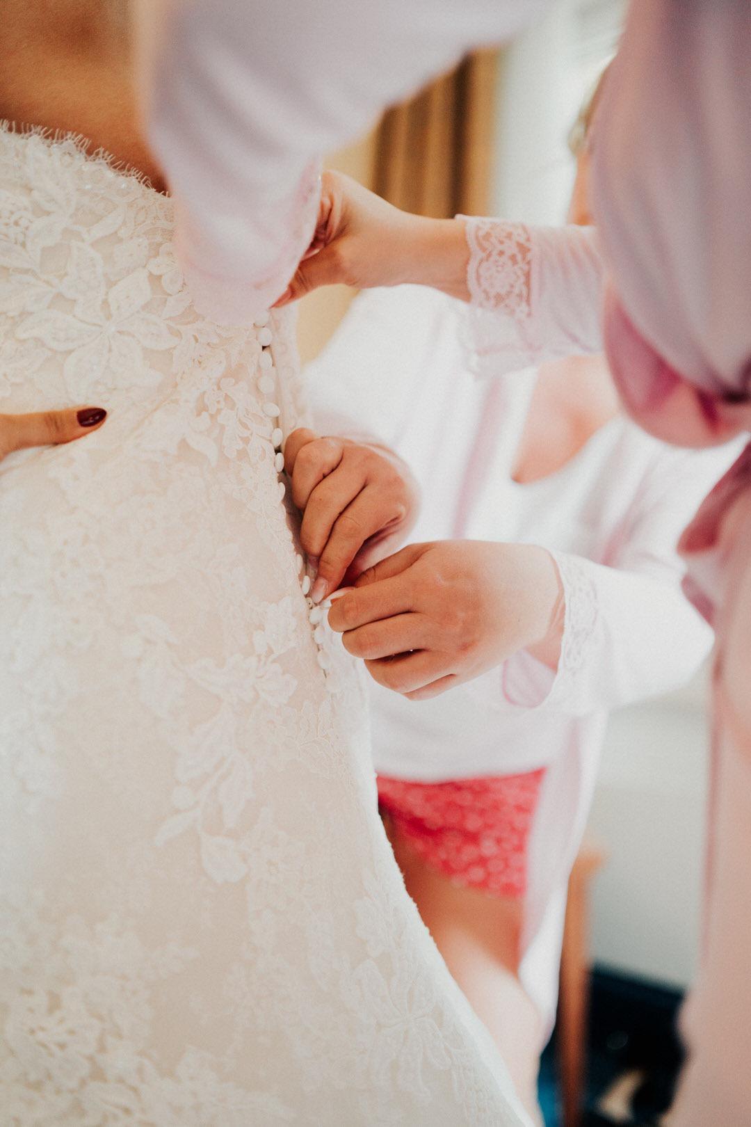 Der Moment bei der Hochzeitsreportage, an dem die Brautjungern das Boho-Kleid zuschnüren bzw. zuknöpfen