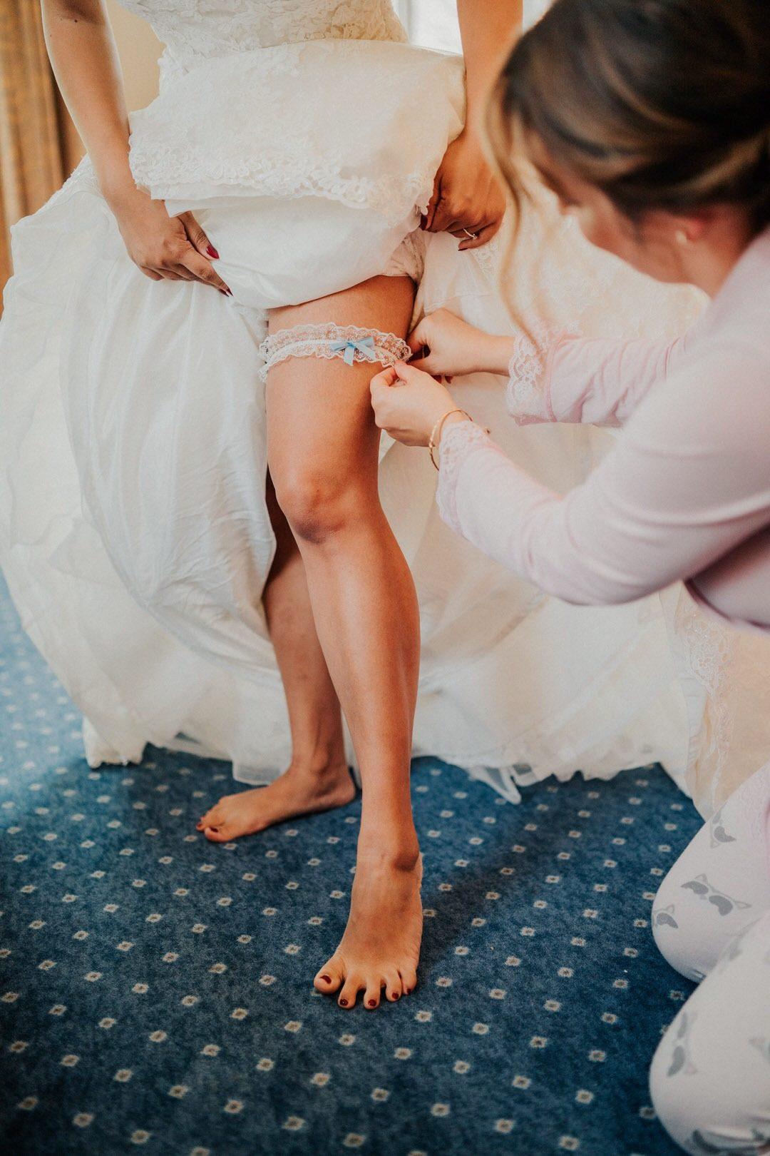 Anziehen des Strumpfbands der Boho-Braut beim Getting Ready