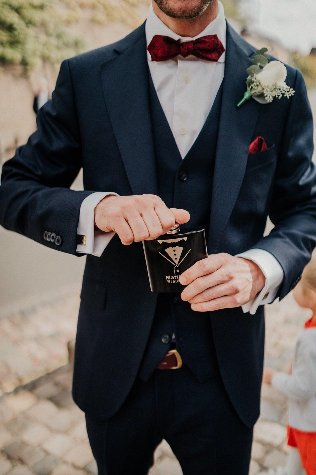 Bräutigam Outfit, Blauer Anzug mit roter Fliege und Bowtie Flachmann vor der Kirchlichen Hochzeit