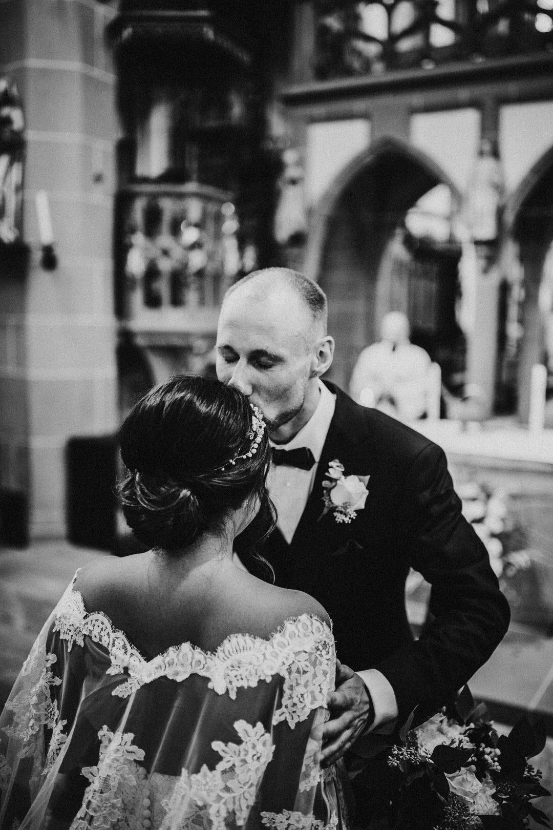 Emotionaler Moment bei den Hochzeitsfotos in der Kirche, ein gerührter Bräutigam küsst seine Braut auf die Stirn