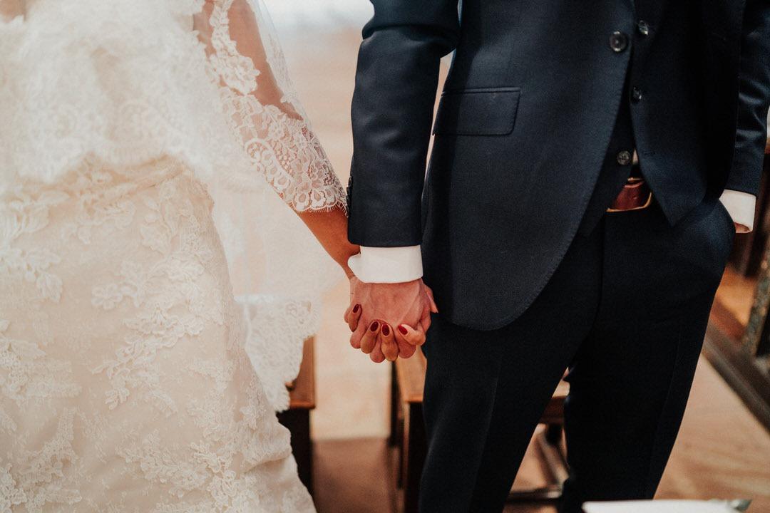 Braut und Bräutigam Hand in Hand in der Kirche