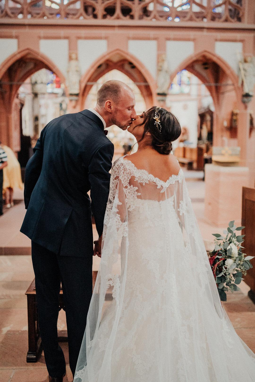 Boho-Brautpaar Kuss während kirchlicher Trauung