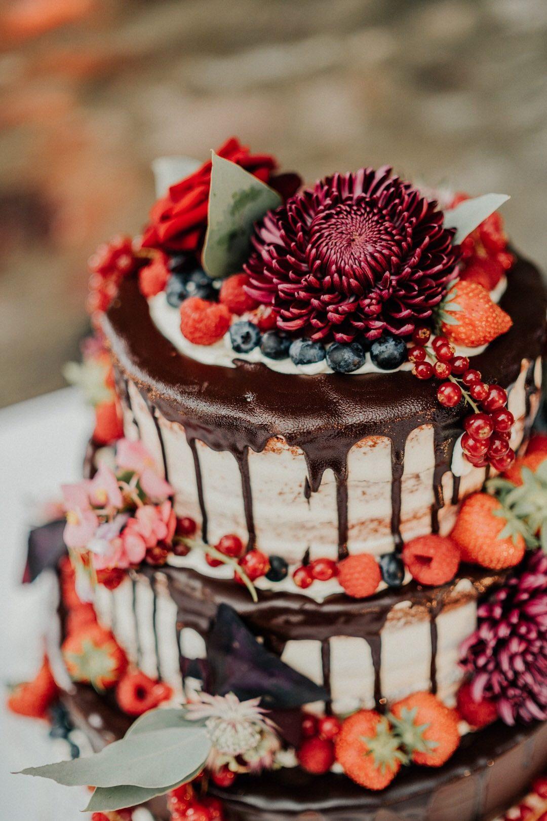 Boho-HOchzeitstorte mit SChokoladenguss, Blumen und Beeren