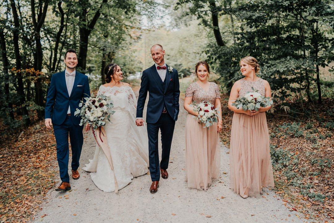 Trauzeuge und Brautjungfern mit dem Hochzeitspaar auf dem Weg zum Fotoshooting