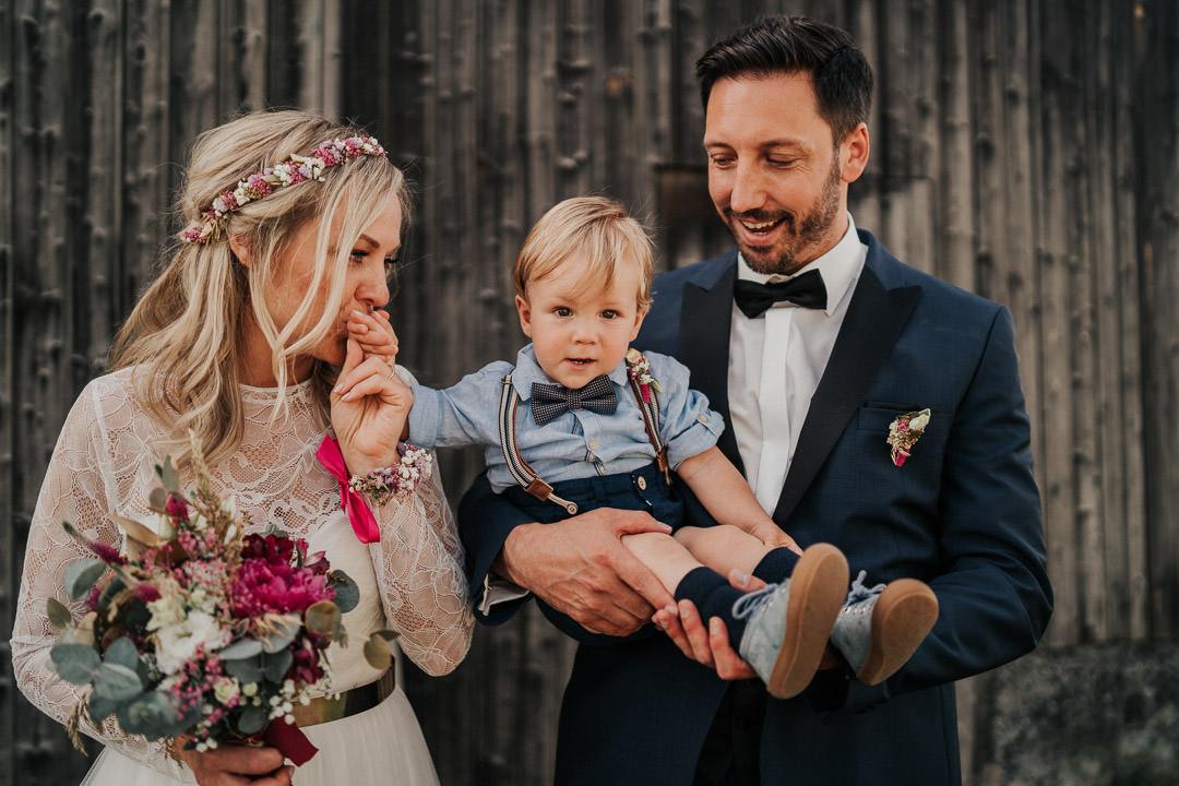 Emotionaler Moment zwischen Brautpaar und Baby